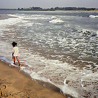 Vijitha Viswanathan (age 9), walks along the shore close to the point where her mother and brother lost their lives. This is the first occasion since the tsunami, that Vijitha has ventured close to the sea...For more information see accompanying notes: Cuddalore_Viswanathan..Photo: Tom Pietrasik.Cuddalore, Tamil Nadu, India.November 2005..THIS PHOTOGRAPH IS THE COPYRIGHT OF TOM PIETRASIK. THE PHOTOGRAPH MAY NOT BE REPRODUCED IN ANY FORM OTHER THAN THAT FOR WHICH PERMISSION WAS GRANTED. THE PHOTOGRAPH MAY NOT BE MANIPULATED WITHOUT PRIOR PERMISSION FROM TOM PIETRASIK...Tom Pietrasik.PHOTOGRAPHER.NEW DELHI.India tel: +91 9810614419.UK tel: +44 7710507916.Email: tom@tompietrasik.com.Website: tompietrasik.com