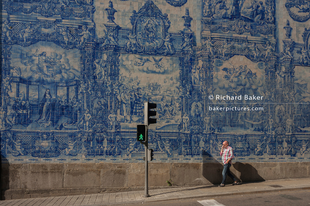 A man walks beneath traditional Azulejo tiles on the wall of Capela Das Almas (church), on Rua Santa Catarina Porto, Portugal. The panels depict scenes from the lives of various saints including the death of St Francis and the martyrdom of St Catherine. Eduardo Leite painted the tiles in a classic 18th-century style, though they actually date back only to the early 20th century.