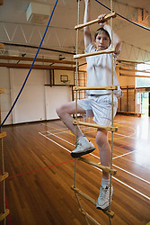 Secondary school student climbing rope ladder in school sports hall,