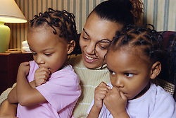 Mother sitting and talking with twin girls,