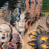 Carnival masks superimposed on water reflections