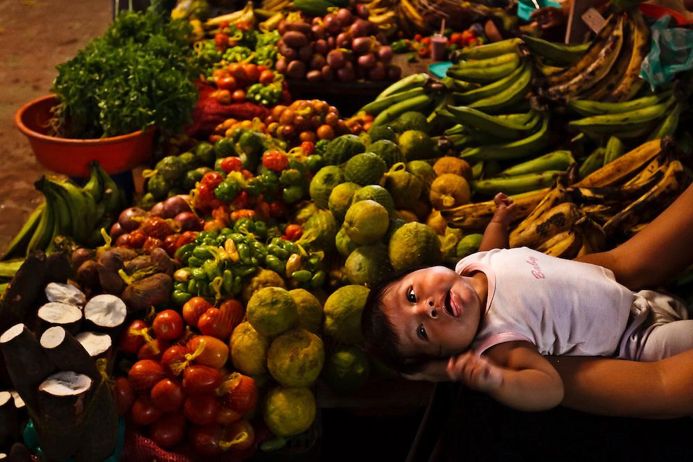 Colombia, Leticia, 2010. Vida nueva. <br /> Plaza de mercado en Leticia. Hasta aqu&iacute; llegan las m&aacute;s diversas y ex&oacute;ticas cosechas de la selva amaz&oacute;nica: araz&aacute;, yuca, pl&aacute;tano, tomate, aj&iacute;es de distintas variedades, cilantro, cebolla. La tierra, el agua y la mujer ind&iacute;gena son muestra de la enorme fertilidad caracter&iacute;stica de la regi&oacute;n. Esta adolescente trabaja junto a su beb&eacute;, a&uacute;n en brazos, en la plaza que sirve para distribuir desde alimentos hasta tel&eacute;fonos celulares, art&iacute;culos de hogar, maquinaria, ropa.<br /> New life. <br /> Leticia Market square. Here the diverse and exotic harvests arrive from the Amazonian forest: araz&aacute;, yucca, banana, tomato, peppers of different varieties, coriander, and onion. The land, water and the indigenous woman are sample of the enormous fertility which characterizes the region. This teenager works together with her baby, still in arms, in the square that trades in a range of goods; foods to cellular telephones, household articles, machinery, and clothes.