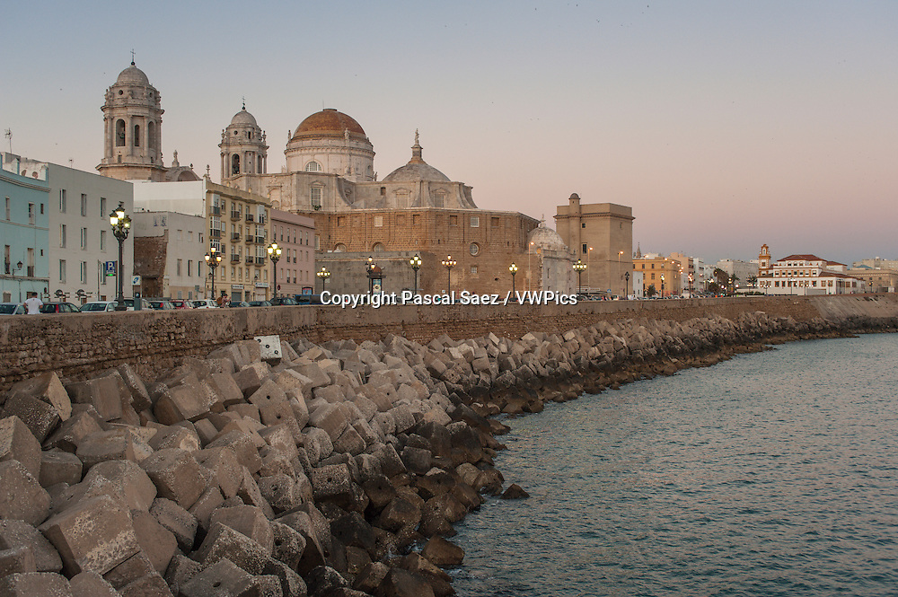 Cádiz cathedral seen at sunset, along the Campo del Sur seafront promenade.