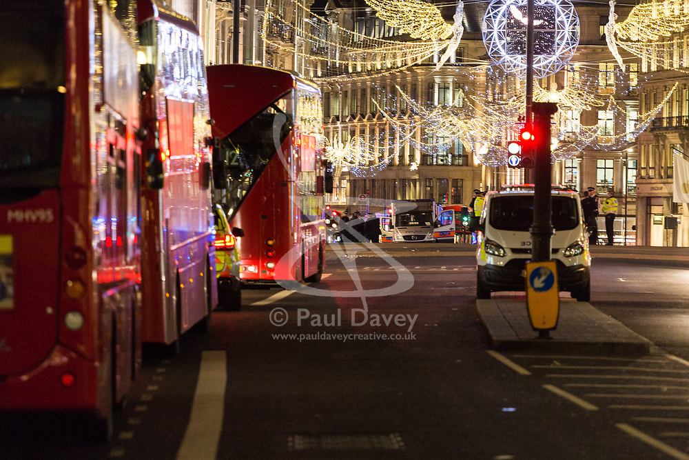 London, November 24 2017. Oxford Circus is sealed off after reports of an incident, creating havoc for traffic and underground commuters during Friday's rush hour, with police eventually standing down. Social media reports mentioned shots fired although this appears now not to be the case PICTURED: Christmas lights illuminate police officers working in the distance at Oxford Circus. © Paul Davey