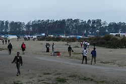 October 25, 2016 - Calais, France - Migrants run through a fallow land in the jungle of Calais  in Calais, France, on 25 October 2016. Up to the evening, about 4,000 migrants from the Refugee camp on the coast at the English Channel were distributed to several regions in France. The police have begun to tear down the huts and tents in the camp. (Credit Image: © Markus Heine/NurPhoto via ZUMA Press)
