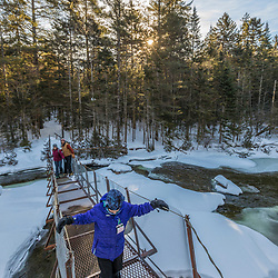 A girl and her parents cross a suspension bridge over the Hudson River near its source in New York's Adirondack Mountains. Upper Works Trail, East River Trail. Tahawus Tract, Newcomb, New York.