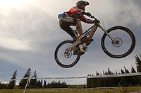 JEROME A. POLLOS/Press..A downhill mountain biker clears a jump on the straightaway section of the course.