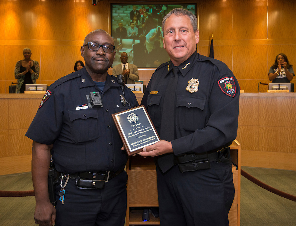 Chief Robert Mock, right, presents Officer Eric Grant, left, with the October Employee of the Month recognition during a meeting of Houston ISD Board of Trustees, September 8, 2016.