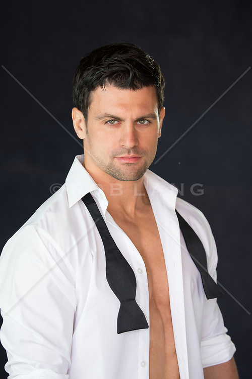 hot man with dark hair and green eyes in an open tuxedo shirt