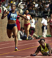 Kelli White, left, of Team USA Blue runs the anchor leg as she crosses the finish line, while Jamaica's Tayna Lawrence falls, during the USA vs the World Women's 4x200m relay at the Penn Relays, Saturday, April 27, 2002, in Philadelphia. Team USA Blue won the race with a time of 1:30.87. (Photo by William Thomas Cain/photodx.com)
