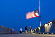 Highland, New York - A few people remain by the American flag at the center of the Walkway over the Hudson after a Memorial Day ceremony there on May 27, 2012.