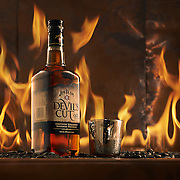 Bottle of Jim Beam Devil's Cut with a small glass surrounded but copper and flames.