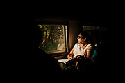 A commuter on the early morning train from Colombo to Kandy is illuminated by the sun shining through a window.