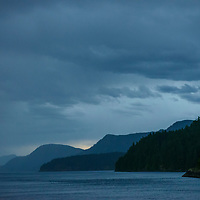 Layers of blue mountains at dusk on the Georgia Strait in the Inside Passage of British Columbia, Canada.