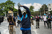 01 DECEMBER 2013 - BANGKOK, THAILAND: Thai anti-government protestors taunt Thai riot police in Bangkok. Thousands of anti-government Thais confronted riot police at Phanitchayakan Intersection, where Rama V and Phitsanoluk Roads intersect, next to Government House (the office of the Prime Minister). Protestors threw rocks, cherry bombs, small explosives and Molotov cocktails at police who responded with waves of tear gas and chemical dispersal weapons. At least four people were killed at a university in suburban Bangkok when gangs of pro-government and anti-government demonstrators clashed. This is the most serious political violence in Thailand since 2010.    PHOTO BY JACK KURTZ<br /> Flip the bird