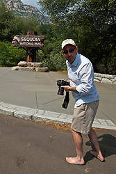 A male adult photographer in bare feet standing in front of the entrance sign to Sequoia National Park, California, United States of America