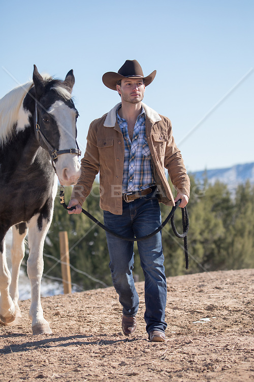 cowboy walking with a horse