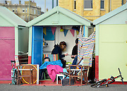 © Licensed to London News Pictures. 02/02/2013. Brighton, UK A family enjoy a beach hut. People enjoy the winter sun at Brighton sea front today 2nd February 2013. Photo credit : Stephen Simpson/LNP