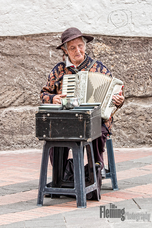A street musician singing and playing her accordion.