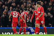 Martin Skrtel of Liverpool (2nd left) looks down at Diego Costa of Chelsea (centre) after the Chelsea player went to ground in the penalty box during the Capital One Cup Semi Final 2nd Leg match between Chelsea and Liverpool at Stamford Bridge, London, England on 27 January 2015. Photo by David Horn.