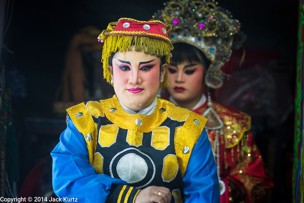 """25 JANUARY 2014 - BANG LUANG, NAKHON PATHOM, THAILAND: Performers with the Sing Tong Teochew opera troupe take the stage during a show in a Chinese shrine in the town of Bang Luang, Nakhon Pathom, Thailand. The Sing Tong Teochew opera troupe has been together for 60 years and travels through central Thailand and Bangkok performing for mostly ethnic Chinese audiences. Chinese opera was once very popular in Thailand, where it is called """"Ngiew."""" It is usually performed in the Teochew language. Millions of Chinese emigrated to Thailand (then Siam) in the 18th and 19th centuries and brought their cultural practices with them. Recently the popularity of ngiew has faded as people turn to performances of opera on DVD or movies. There are still as many 30 Chinese opera troupes left in Bangkok and its environs. They are especially busy during Chinese New Year when travel from Chinese temple to Chinese temple performing on stages they put up in streets near the temple, sometimes sleeping on hammocks they sling under their stage.     PHOTO BY JACK KURTZ"""