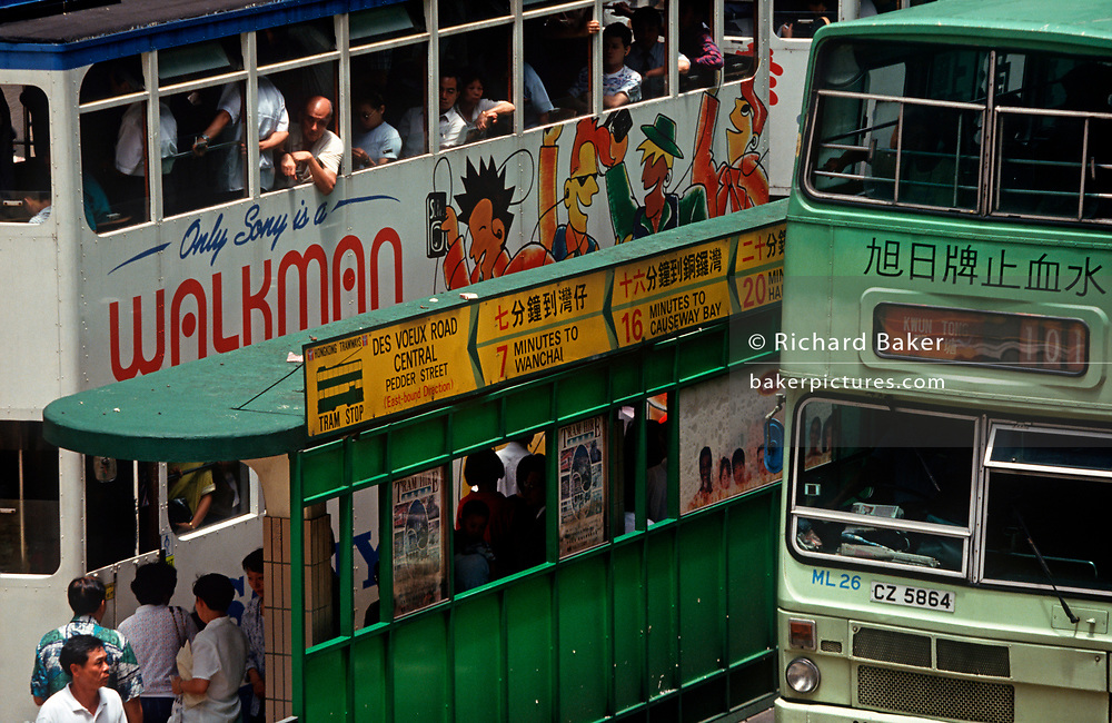 While still a British colony, 1990s tram passenger commuters stop at a tram and bus stop on the des Voeux road in the direction of Wanchai and Causeway Bay, on 21st April 1995, in Central, Hong Kong, China. (Photo by Richard Baker / In Pictures via Getty Images)