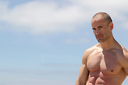 portrait of a man with no shirt and a shaved head