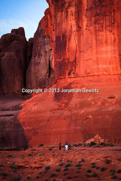 Rock formations whose red color is accentuated by morning sunlight tower over visitors in Arches National Park, Utah. WATERMARKS WILL NOT APPEAR ON PRINTS OR LICENSED IMAGES.<br />