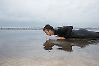 Man in wetsuit doing pushups in shallow water on beach side view