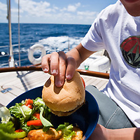 A crew member holds his lunch before eating as he eats his food while on watch as the large sailing yacht crosses the Atlantic Ocean.