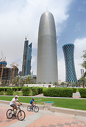 People cycling on The Corniche promenade with high rise office buildings to rear in Doha Qatar