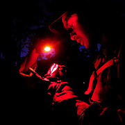 October 10, 2008 -- GULFPORT, Miss. U.S. Navy Master-at-Arms 2nd Class Lawrence Limson plots a point on a map at night as part of a land navigation course at Expeditionary Combat Skills School (ECS).  <br />