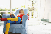 Young boy (7-9) sitting in armchair reading wearing superhero costume