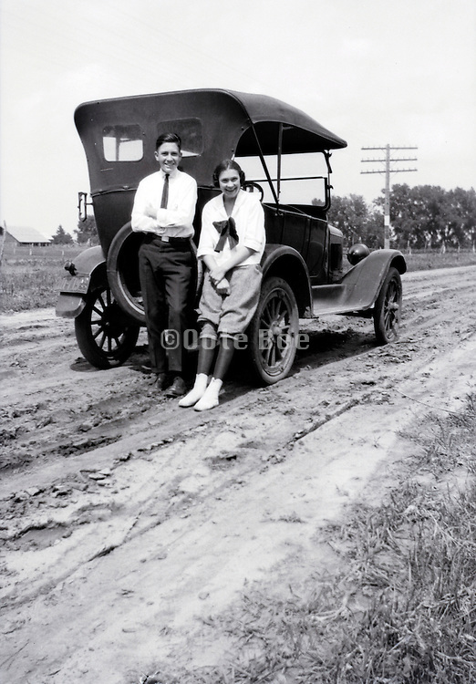 couple posing by their car on muddy road USA Missouri 1920s