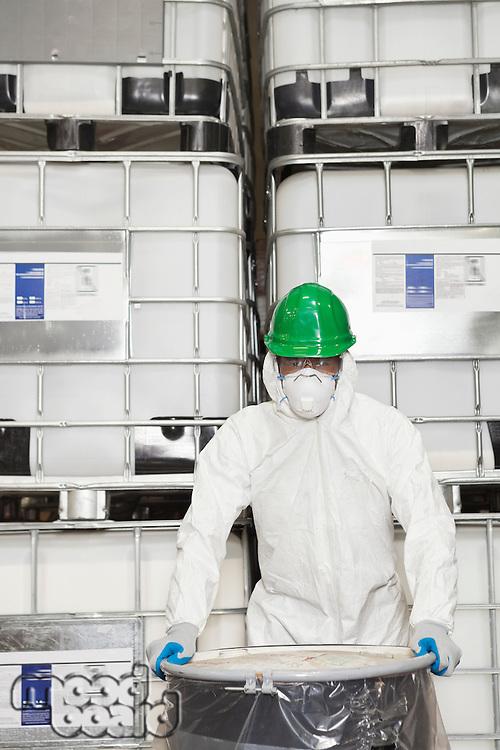 Technician in hazmat suit holding plastic covered chemical drum