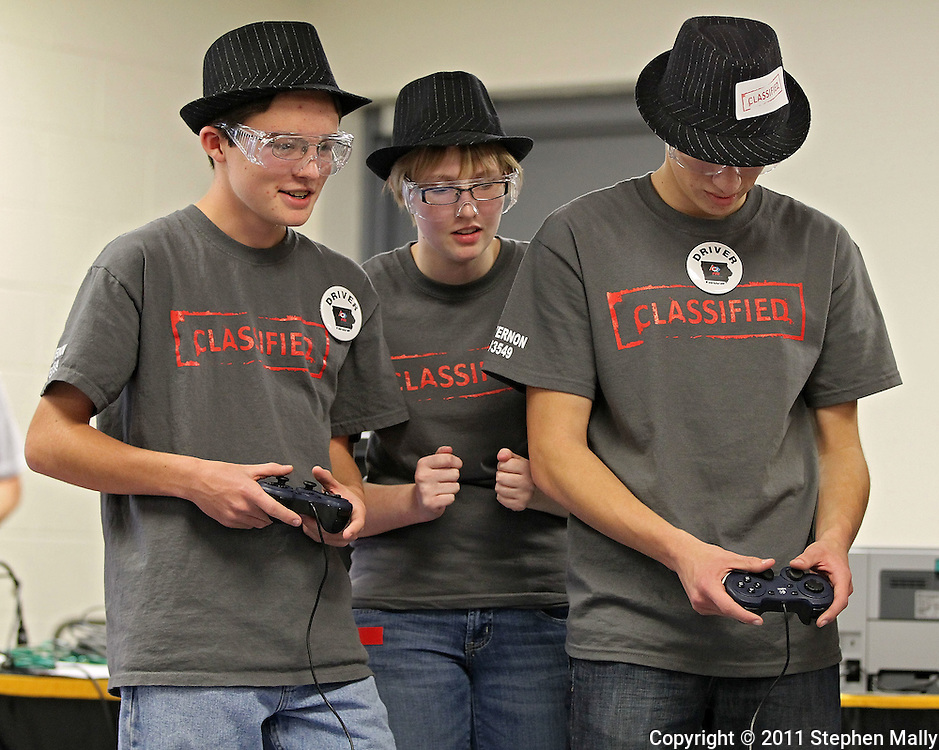 Gage Lochner (from left), 14, freshman, Catie Scheehy, 17, senior, and Drew Keller, 16, sophomore of Mount Vernon High School, participate in a qualification match at the FTC Qualifying Tournament held at Linn-Mar High School at 3111 North 10th Street in Marion on Saturday November 19, 2011. (Stephen Mally/Freelance)