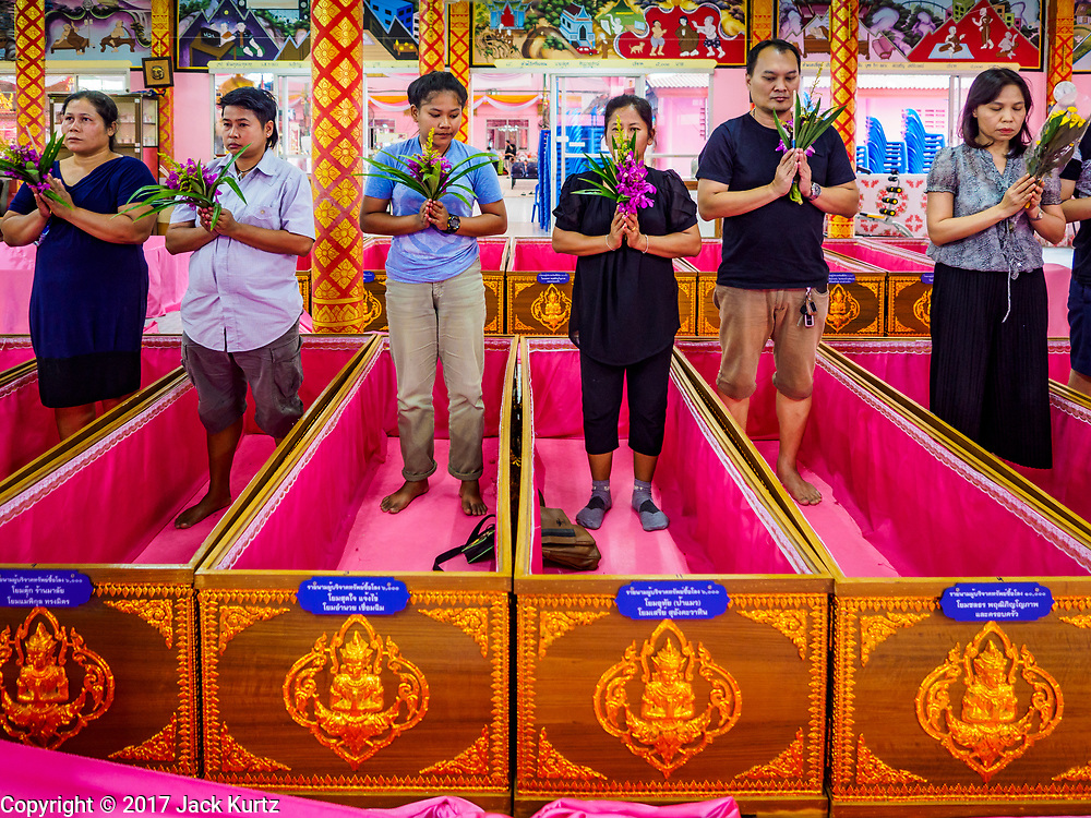 """29 MARCH 2017 - BANG KRUAI, NONTHABURI, THAILAND: People about to go through their ritualistic death during a """"Resurrection Ceremony"""" stand in their coffins at Wat Ta Kien (also spelled Wat Tahkian), a Buddhist temple in the suburbs of Bangkok. People go to the temple to participate in a """"Resurrection Ceremony."""" Groups of people meet and pray with the temple's Buddhist monks. Then they lie in coffins, the monks pull a pink sheet over them, symbolizing their ritualistic death. The sheet is then pulled back, and people sit up in the coffin, symbolizing their ritualist rebirth. The ceremony is supposed to expunge bad karma and bad luck from a person's life and also get people used to the idea of the inevitability of death. Most times, one person lays in one coffin, but there is family sized coffin that can accommodate up to six people. The temple has been doing the resurrection ceremonies for about nine years.          PHOTO BY JACK KURTZ"""