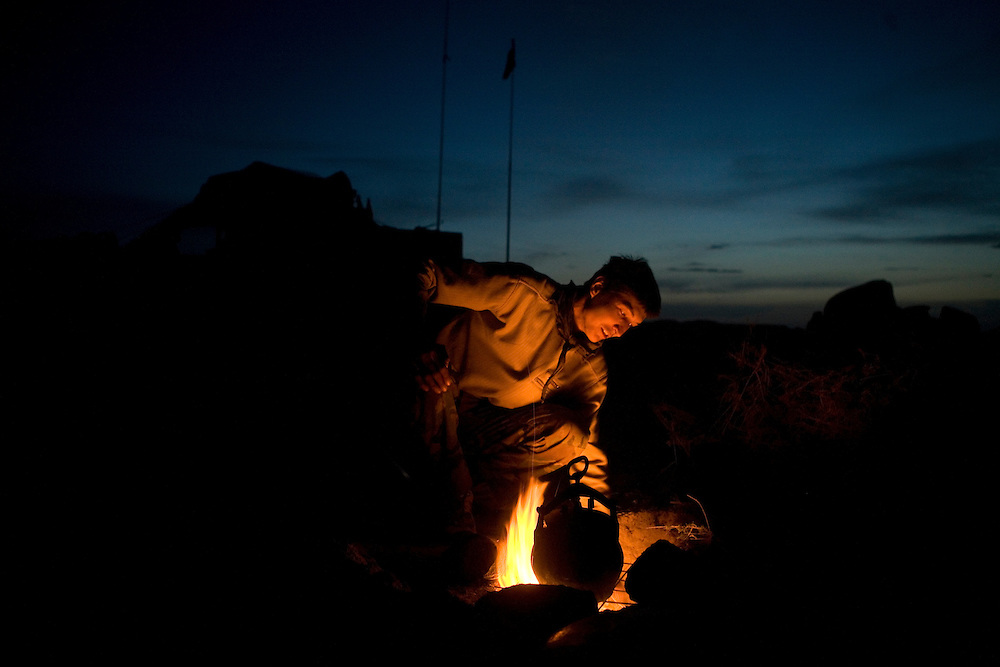 Members of the Afghan National Army cook dinner after a day of hunting the Taliban in the Manjul valley, Kandahar province, Afghanistan on Friday, March 23, 2007.
