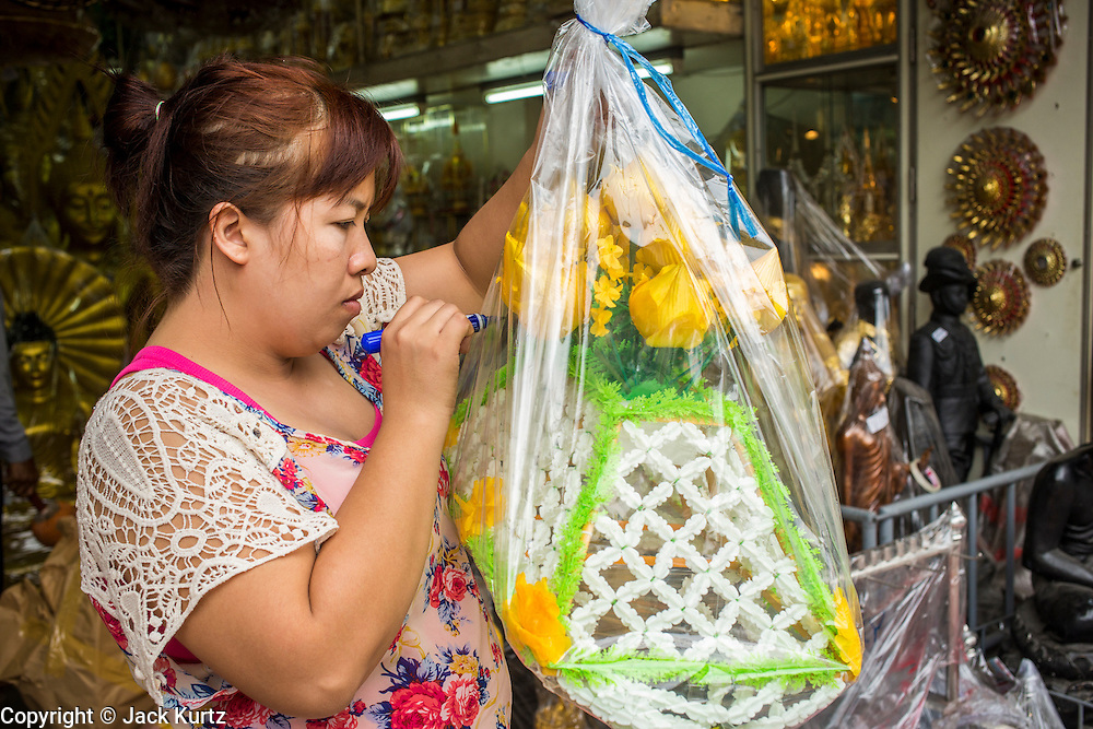 "12 NOVEMBER 2012 - BANGKOK, THAILAND:   A store clerk prices a pre made alms basket for sale in a shop on Bamrung Muang Street in Bangkok. Thanon Bamrung Muang (Thanon is Thai for Road or Street) is Bangkok's ""Street of Many Buddhas."" Like many ancient cities, Bangkok was once a city of artisan's neighborhoods and Bamrung Muang Road, near Bangkok's present day city hall, was once the street where all the country's Buddha statues were made. Now they made in factories on the edge of Bangkok, but Bamrung Muang Road is still where the statues are sold. Once an elephant trail, it was one of the first streets paved in Bangkok. It is the largest center of Buddhist supplies in Thailand. Not just statues but also monk's robes, candles, alms bowls, and pre-configured alms baskets are for sale along both sides of the street.    PHOTO BY JACK KURTZ"