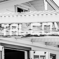 Laguna Beach Crystal Cove sign black and white panorama picture of cottage #46. The famous Cottage 46 is now an exhibitors center operated by the Crystal Cove Alliance. The cottage is part of the Crystal Cove Historic District in Orange County Southern California.