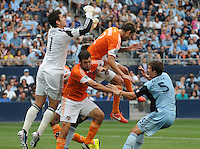 Football - Major League Soccer - Houston Dynamo at Sporting KC - The Sporting KC and the Houston Dynamo played to a 1-1 tie in regulation time at Sporting KC Park in Kansas City, Kansas, USA. Houston Dynamo goalkeeper Tally Hall (1, left) leaps over Houston Dynamo teammates forward Will Bruin (12) and defender Eric Brunner (2) to spike the ball on a corner kick late in the first half.  At far right is Sporting KC defender Matt Besler (5)..