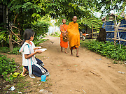 "20 JUNE 2016 - DON KHONE, CHAMPASAK, LAOS:  Girls wait to present alms to monks from Wat Khone Nua on their morning alms' rounds, called the ""tak bat"" in Don Khone village on Don Khone Island. Don Khone Island, one of the larger islands in the 4,000 Islands chain on the Mekong River in southern Laos. The island has become a backpacker hot spot, there are lots of guest houses and small restaurants on the north end of the island.    PHOTO BY JACK KURTZ"