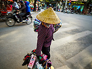 21 DECEMBER 2017 - HANOI, VIETNAM:  A street peddler crosses a road in the old quarter of Hanoi.  PHOTO BY JACK KURTZ