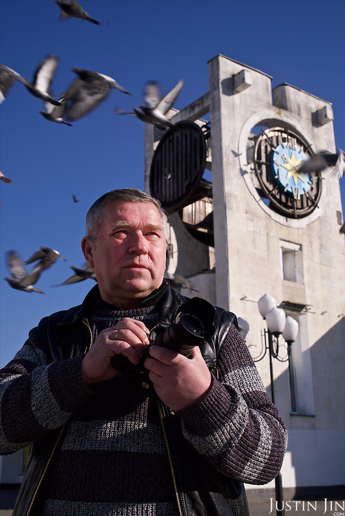 Photographer Vladimir Savran, 65, worked as a photojournalist for seven years (1987 - 1994) inside the radioactive zone after the Chernobyl explosion in 1986. <br /> <br /> He is posing in the main town square of Slavutych, where and now works as a studio photographer. <br /> <br /> Slavutych rises out of the ashes of the Chernobyl nuclear disaster in April 26, 1986. People living near the disaster area were largely moved to the new city, built from scratch for the sole purpose of housing the population displaced by the nuclear accident.
