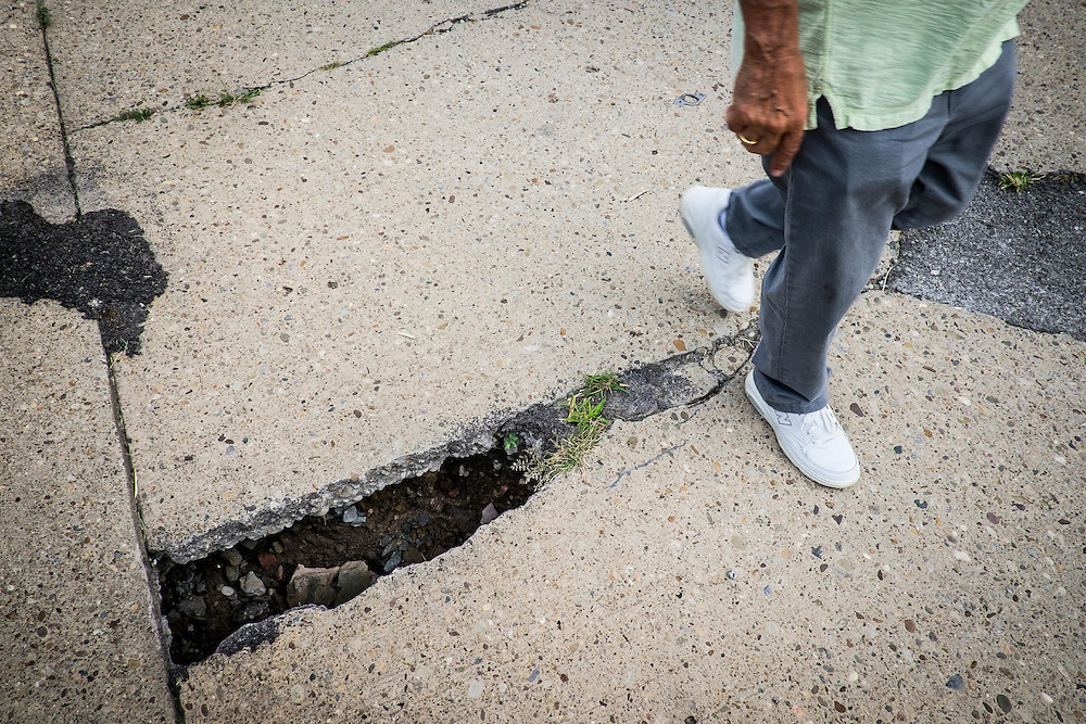 Monessen Mayor Lou Mavrakis walks past an open section of a road in Monessen where the badly decayed 100-year old sewage system is collapsing and the subsequent erosion is undermining the streets and sidewalks. Repairs are estimated to cost between $40 to $50 million.<br /> <br /> He said the city now has 400 blighted homes 30 abandoned downtown buildings and he doesn&rsquo;t have money to tear them down.<br /> <br /> Monessen, a third-class city, faces the same problems as th other former steel towns &mdash; declining population and tax revenue after the mills shut down. The city's population has dropped to 7,600 from a high of 20,268 in 1930.