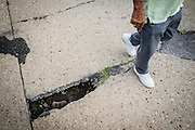 Monessen Mayor Lou Mavrakis walks past an open section of a road in Monessen where the badly decayed 100-year old sewage system is collapsing and the subsequent erosion is undermining the streets and sidewalks. Repairs are estimated to cost between $40 to $50 million.<br /> <br /> He said the city now has 400 blighted homes 30 abandoned downtown buildings and he doesn't have money to tear them down.<br /> <br /> Monessen, a third-class city, faces the same problems as th other former steel towns — declining population and tax revenue after the mills shut down. The city's population has dropped to 7,600 from a high of 20,268 in 1930.