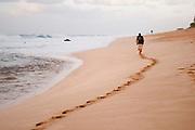 A man walks along the beach leaving footprints in the sand.