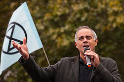 London, UK. 7 October, 2019. Jonathan Bartley, co-leader of the Green Party, addresses climate activists from Extinction Rebellion blocking Millbank in front of Lambeth bridge on the first day of International Rebellion protests to demand a government declaration of a climate and ecological emergency, a commitment to halting biodiversity loss and net zero carbon emissions by 2025 and for the government to create and be led by the decisions of a Citizens' Assembly on climate and ecological justice.