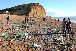 © Licensed to London News Pictures. 19/01/2014. Burton Bradstock, UK High tide has been littering the beaches following the recent storms making it interesting for Sunday walkers at Westbay, Dorset today, 19th January 2014.. Photo credit : Jason Bryant/LNP