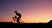 The silhouette of a cyclist (08.09.2009) before the colorful evening sky shortly after sunset on a bike path in old country mountain, Altlandsberg. Germany. Photo:  Robert Schlesinger dpa/lbn +++(c) dpa - report + + +